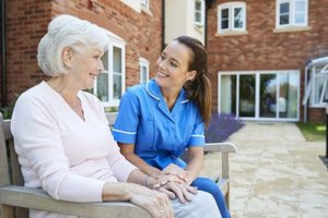 a nurse tends to a woman in senior assisted living